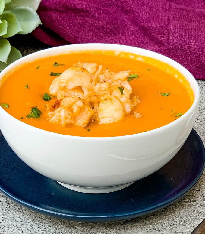 creamy homemade lobster bisque recipe in a white bowl with a purple towel