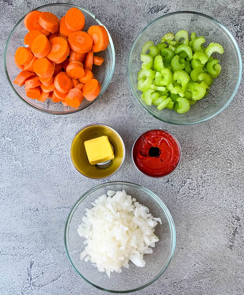 chopped carrots, celery, onions, and butter, and tomato paste in separate bowls
