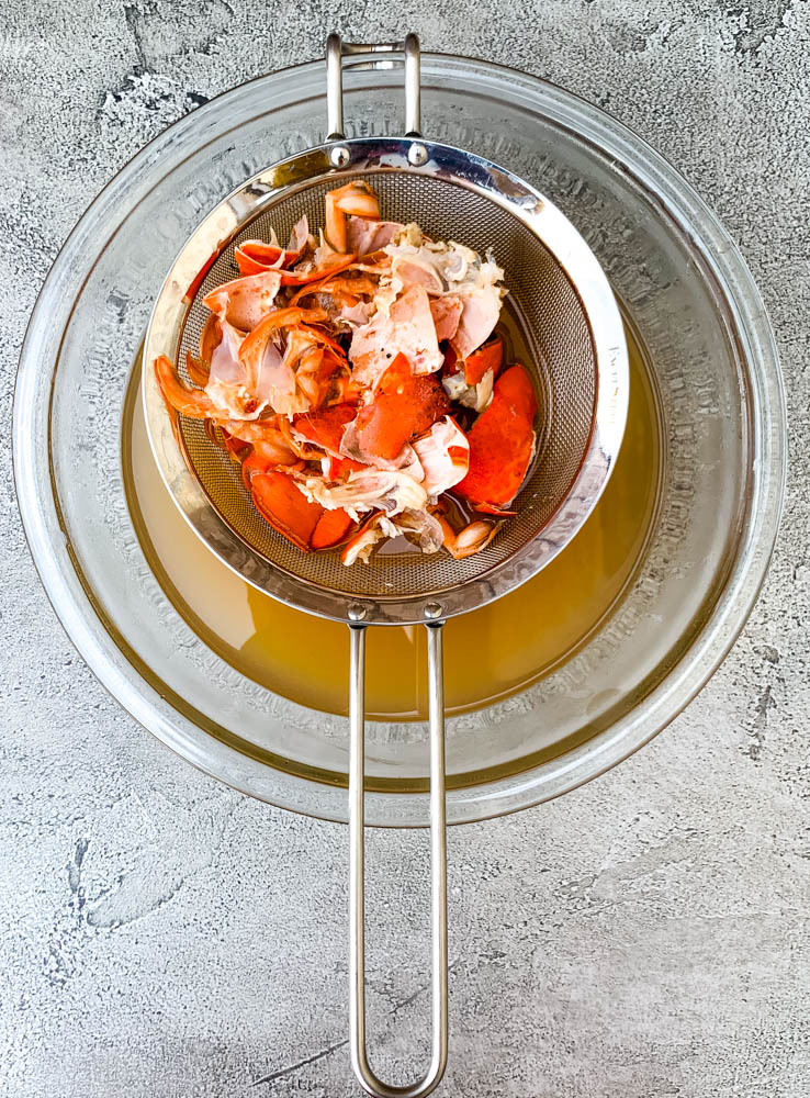 shelled lobster in a strainer with a bowl of lobster stock