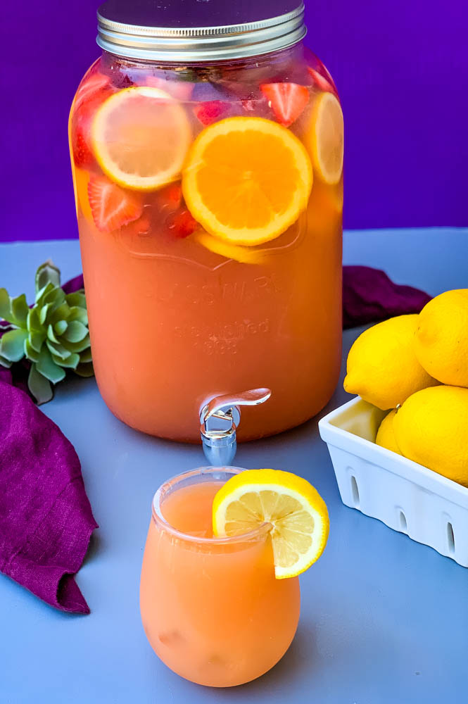 jungle juice cocktail recipe in a 2 gallon glass container with fresh fruit