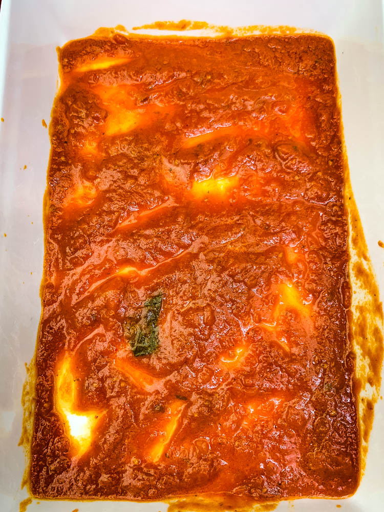 marinara in the bottom of a white baking dish