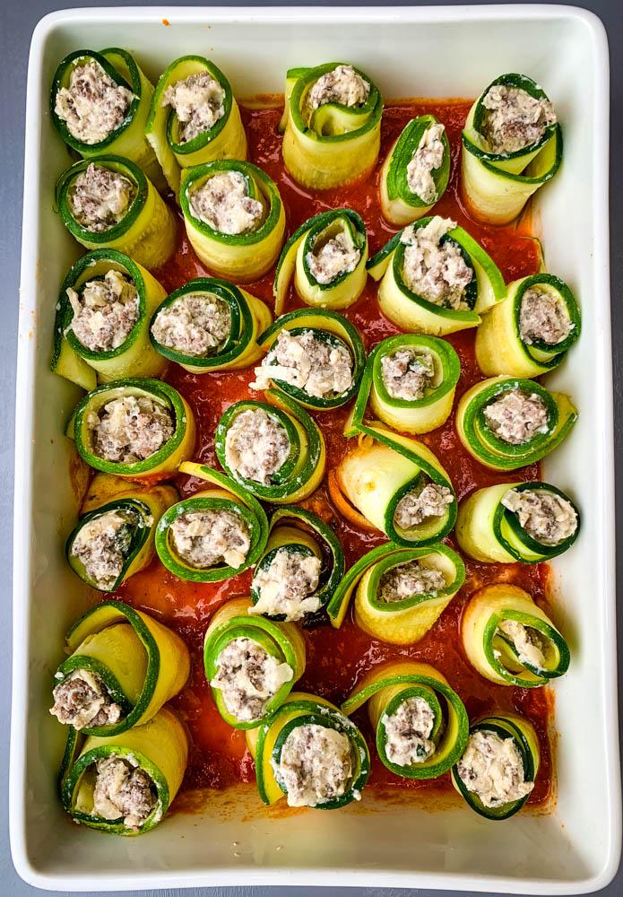 zucchini lasagna rolls in a white baking dish