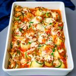zucchini lasagna roll ups in a white baking pan with shredded cheese