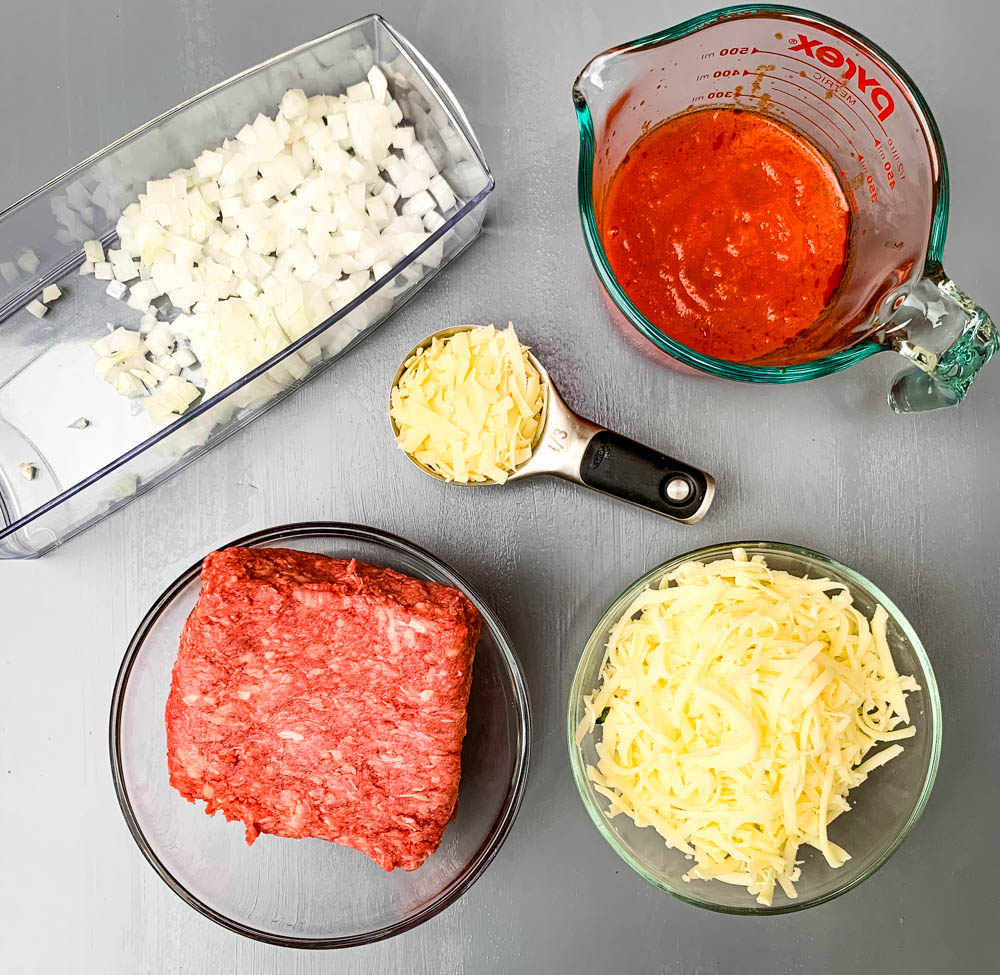 chopped onions, raw ground beef, marinara, and shredded cheese in glass bowls for zucchini lasagna roll ups