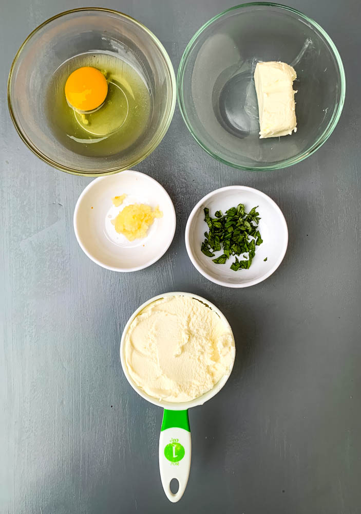 egg, cream cheese, ricotta, garlic, and basil in separate bowls for zucchini lasagna roll ups