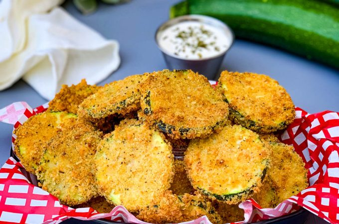 air fryer zucchini chips in a bowl with ranch dressing