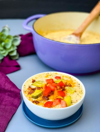 keto low carb cheeseburger soup in a white bowl with pickles, tomatoes, and bacon