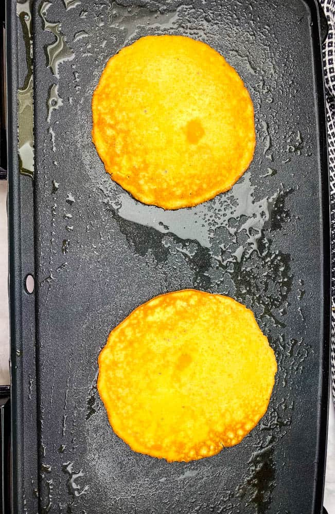 keto low carb pancakes cooking on a griddle