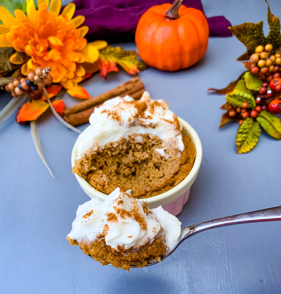 a spoon serving of keto low carb pumpkin mug cake in a pink ramekin with whipped cream