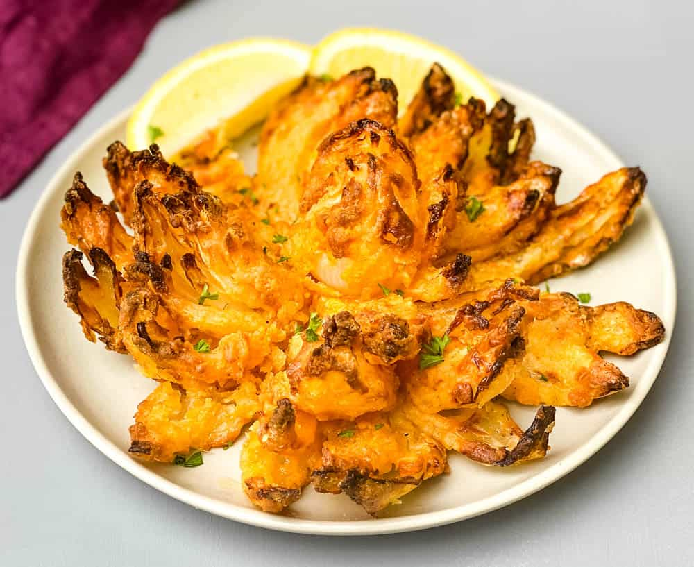 air fryer blooming onion on a plate with sliced lemons