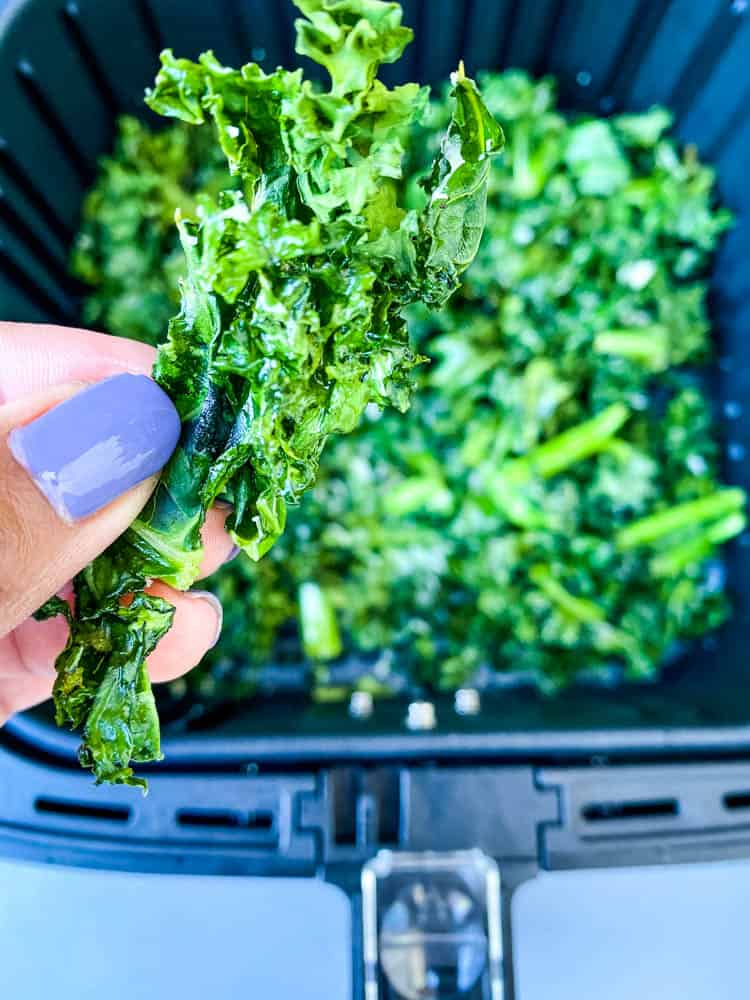 person holding air fryer kale chips
