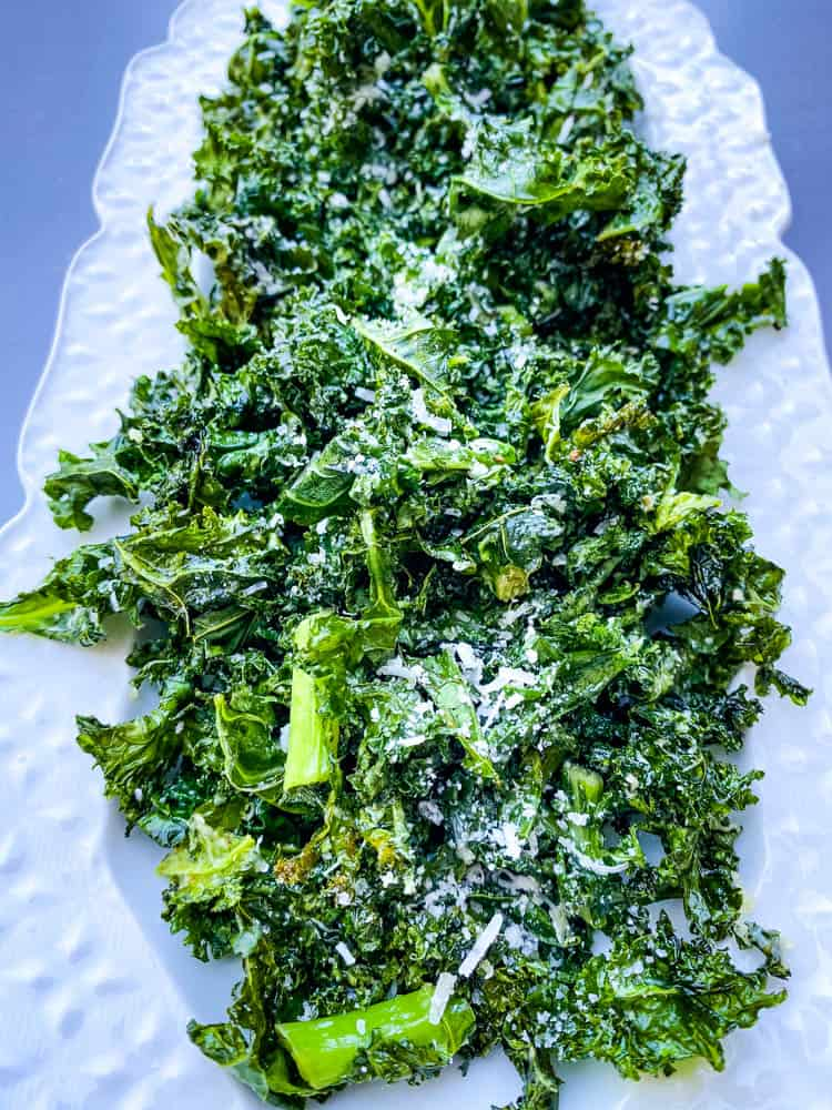 air fryer kale chips on a white plate with parmesan cheese