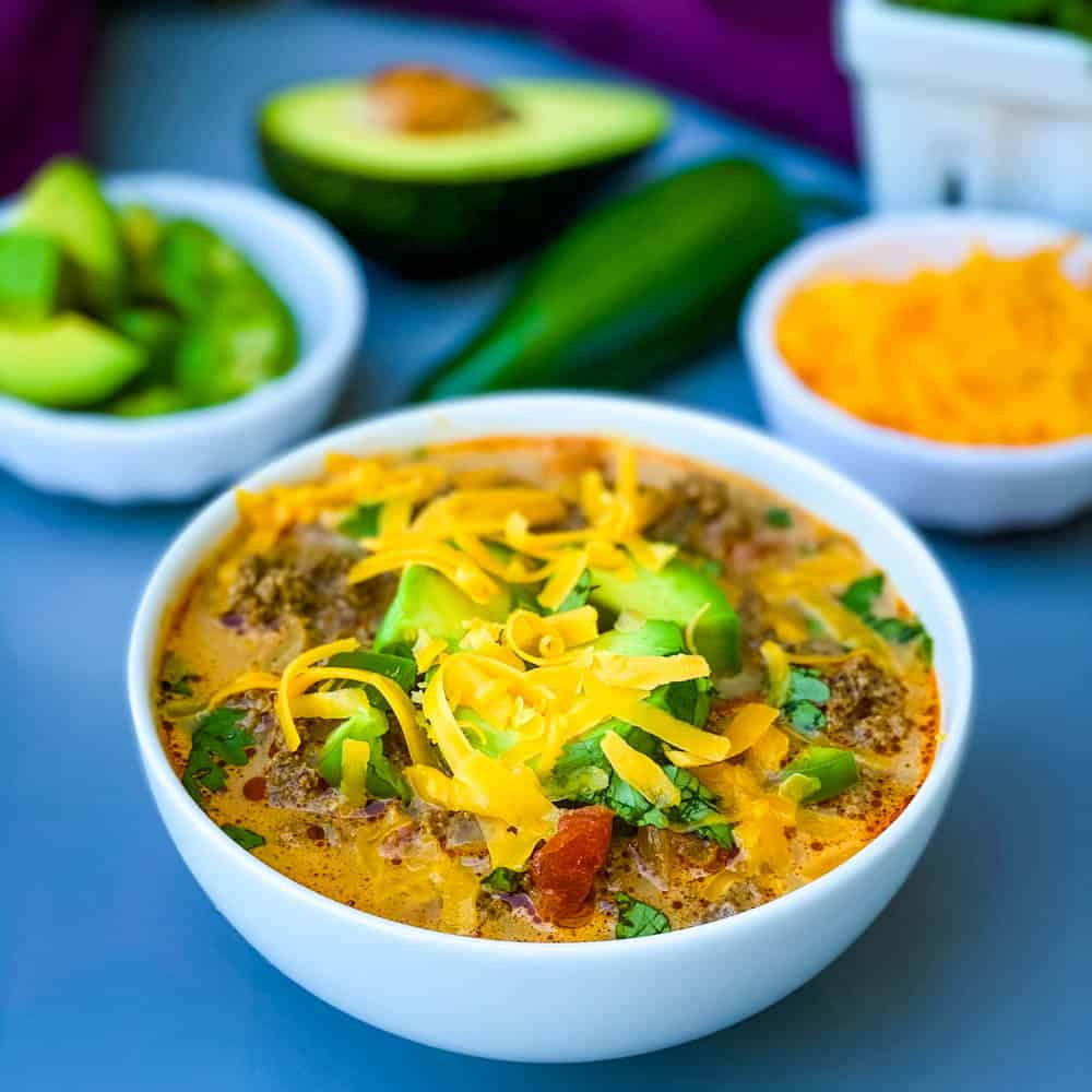 keto low carb taco soup with shredded cheese, avocado, and jalapenos in a white bowl