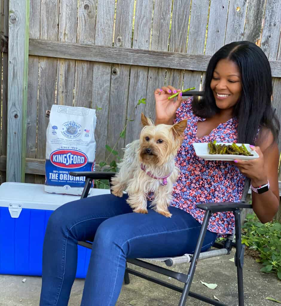 person eating asparagus with a dog on their lap