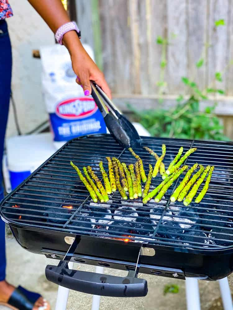 person grilling asparagus on a charcoal grill