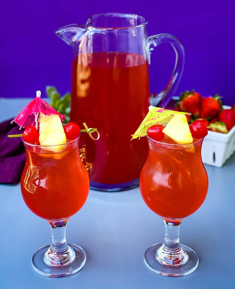 easy rum punch recipe in glasses with pineapple and cherries