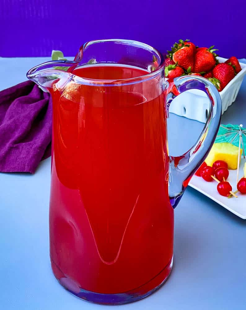 easy rum punch in a glass pitcher with fresh pineapples and cherries