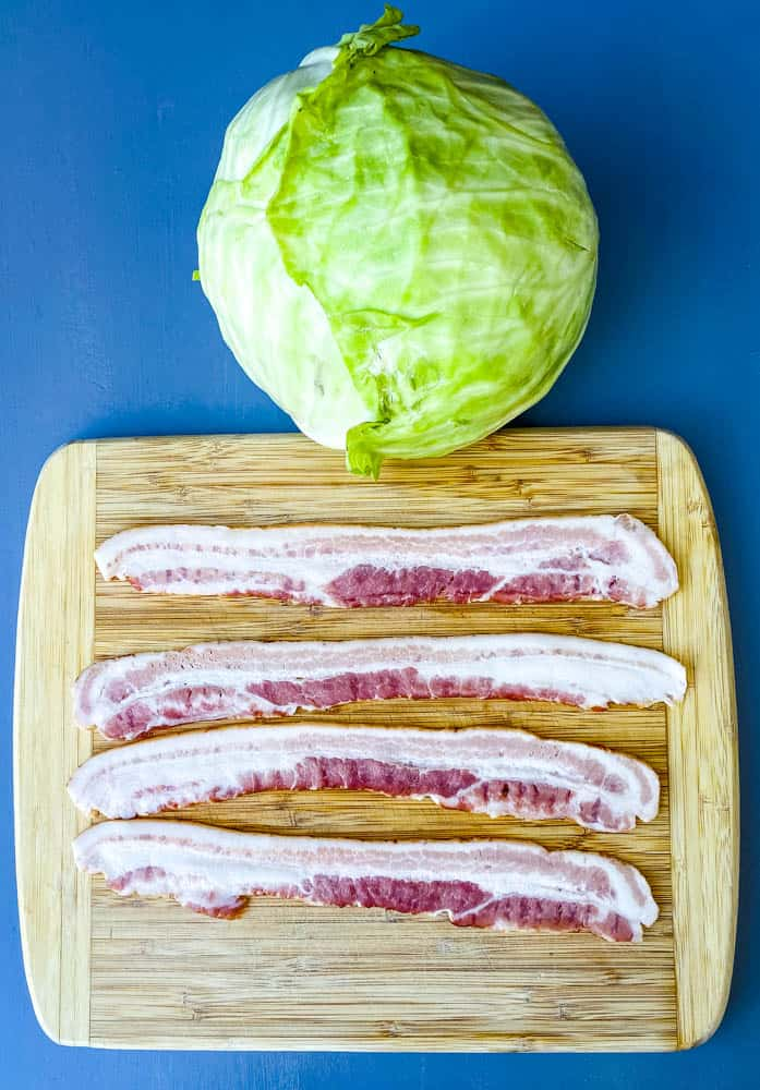 raw green cabbage head and raw bacon slices on a cutting board for southern fried cabbage