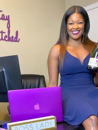 person sitting on a desk with a bottle of champagne