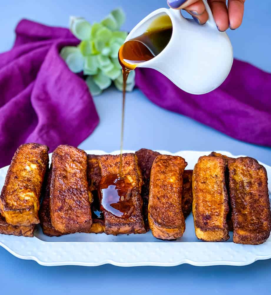 air fryer french toast sticks on a white plate with syrup drizzled throughout