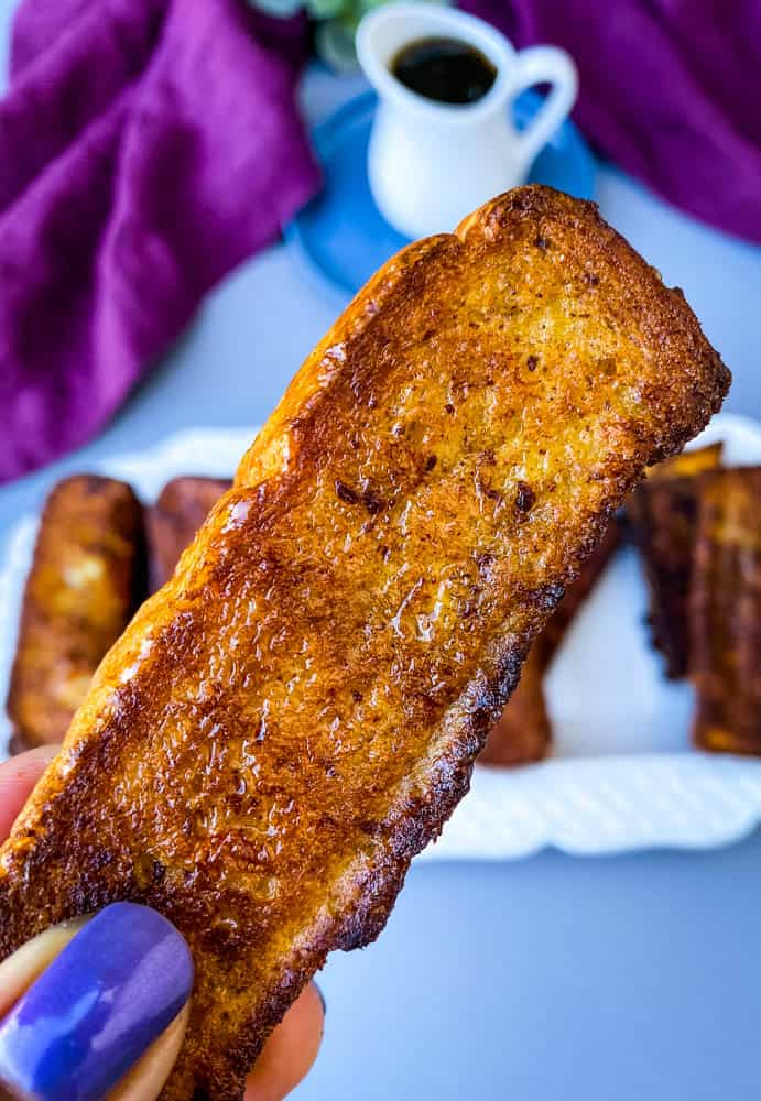 person holding air fryer French toast stick