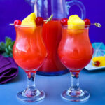 Bahama Mama Recipe in glasses with a pitcher of drink