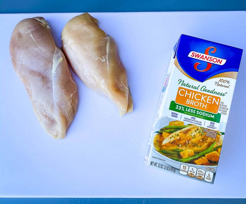 raw chicken breasts on a cutting board with a box of chicken broth