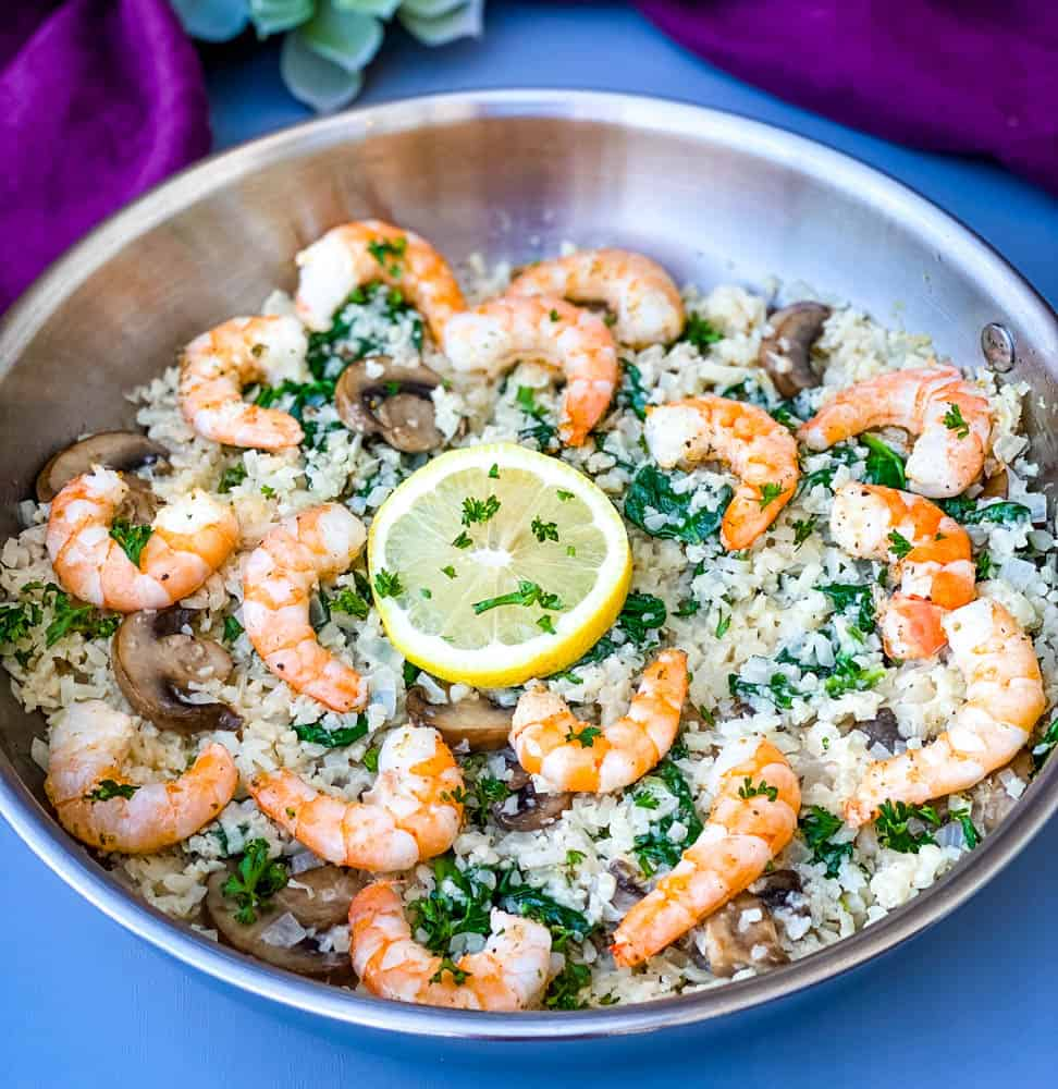 keto low carb cauliflower risotto in a pan with lemon and shrimp