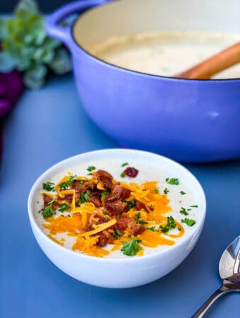 keto low carb cauliflower soup in a white bowl with shredded cheese and bacon