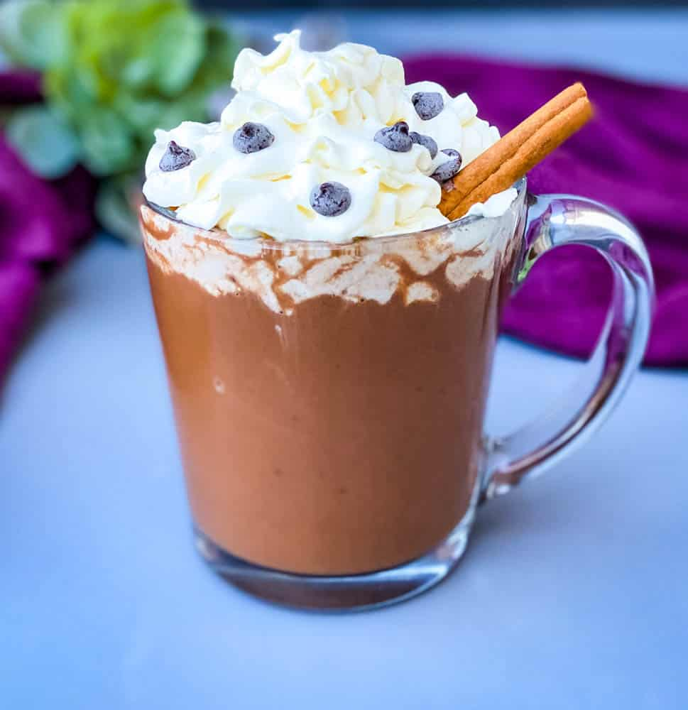 keto low carb hot chocolate in a glass mug with whipped cream and cinnamon and chocolate chips