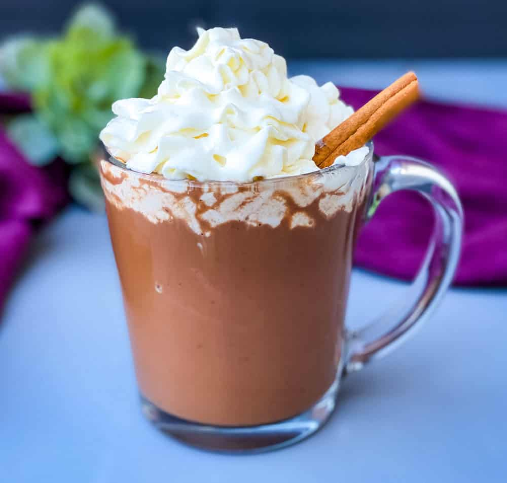 keto low carb hot chocolate in a glass mug with whipped cream and cinnamon