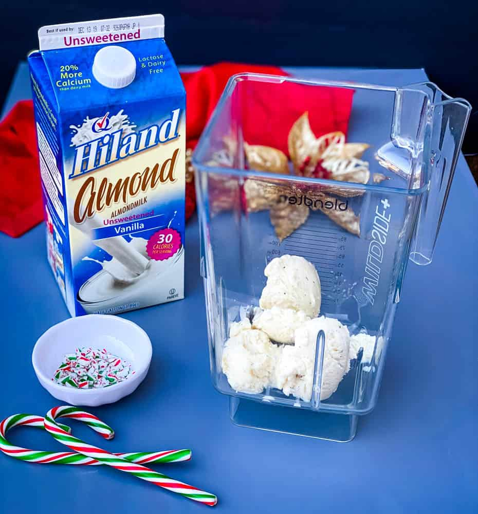 ice cream in a blender with a carton of almond milk for peppermint milkshakes