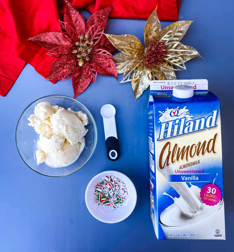 vanilla ice cream in a glass bowl with a carton of almond milk, crushed candy canes and peppermint oil extract for peppermint milkshakes