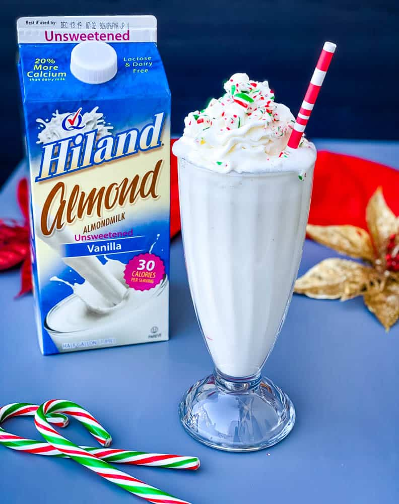 peppermint milkshake with candy canes and whipped cream in a glass with a straw alongside a carton of Almond milk