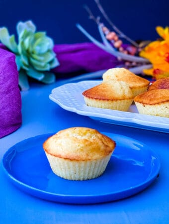air fryer cornbread muffin on a blue plate with several air fryer cornbread muffins on a white plate