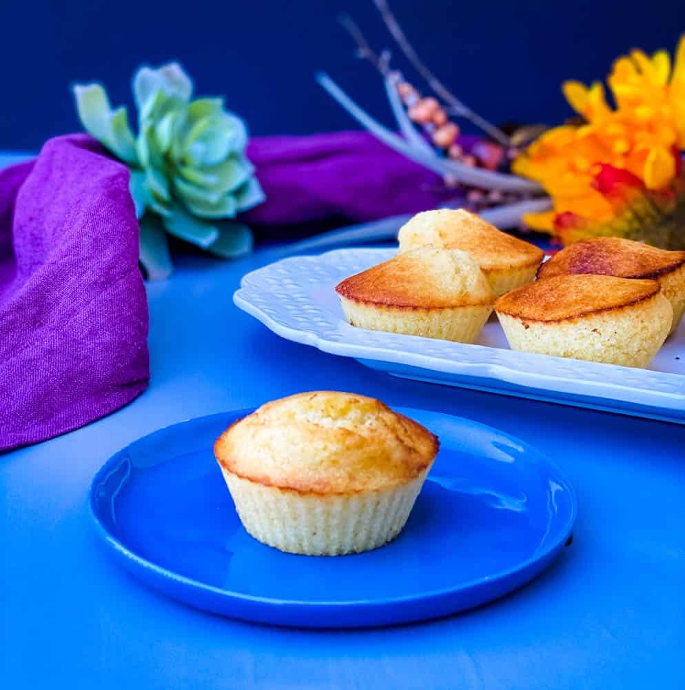 air fryer cornbread muffin on a blue plate with several air fryer cornbread muffins on a white plate