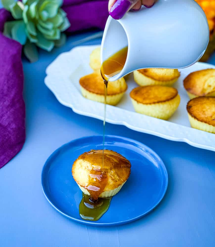 honey being drizzled on air fryer cornbread muffin on a blue plate with several air fryer cornbread muffins on a white plate