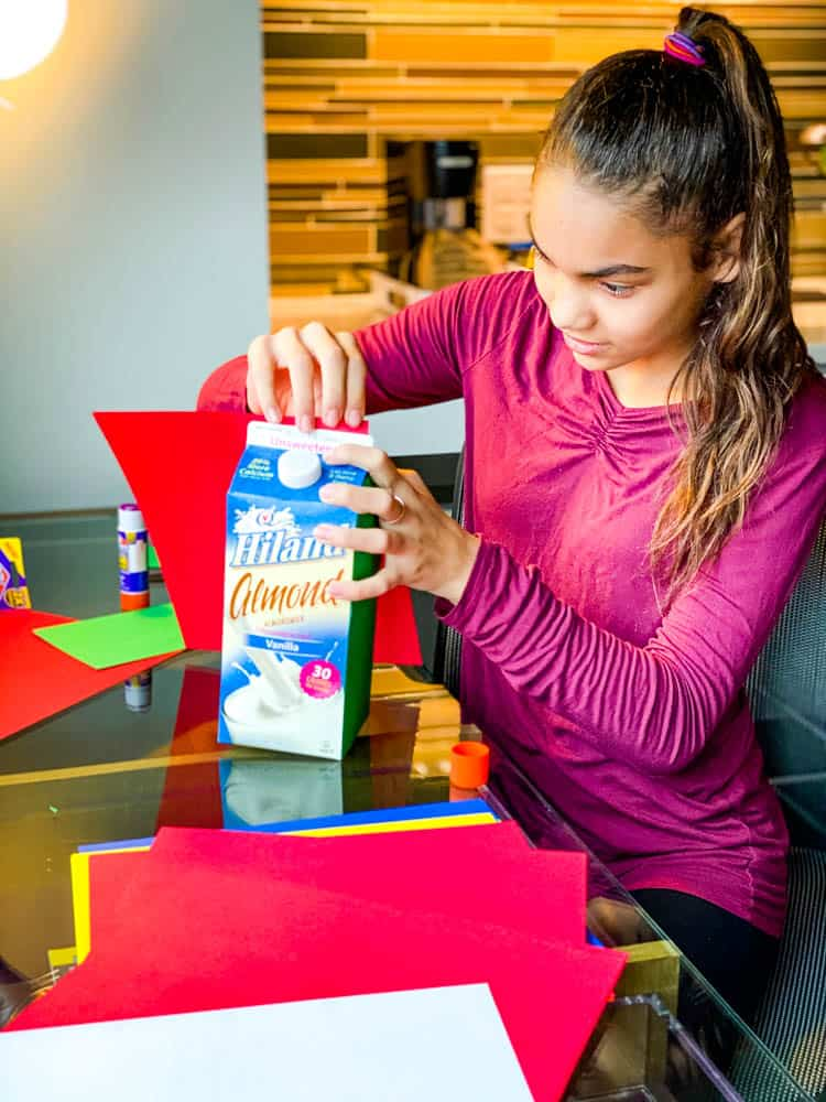 child making Christmas decoration using recycled milk carton