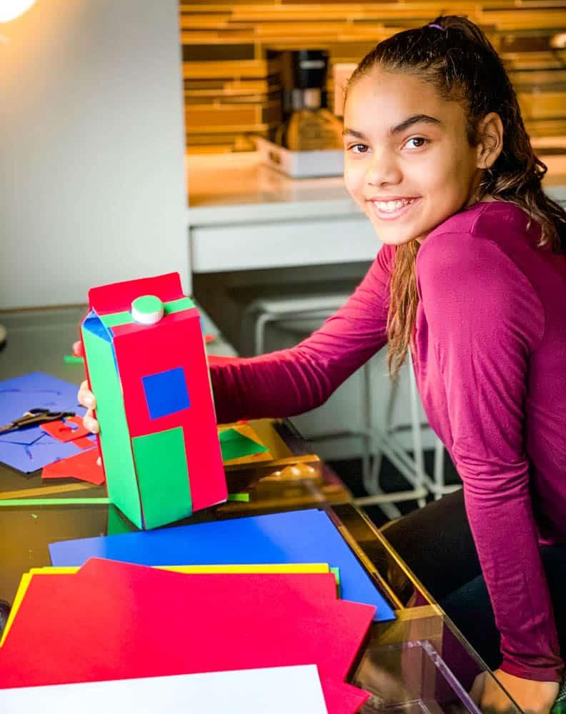 child making Christmas decoration using recycled milk carton