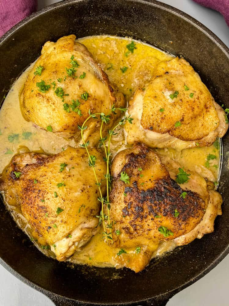 smothered pork chop thighs in a cast iron skillet with gravy
