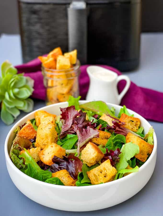 air fryer croutons on a salad in a white bowl