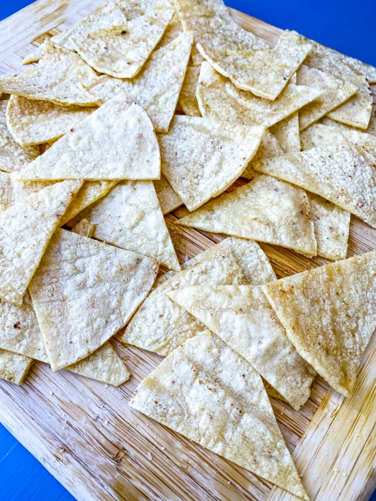 sliced corn tortillas on a cutting board for air fryer tortilla chips
