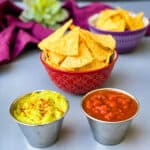 air fryer tortilla chips in a red bowl with guacamole and salsa