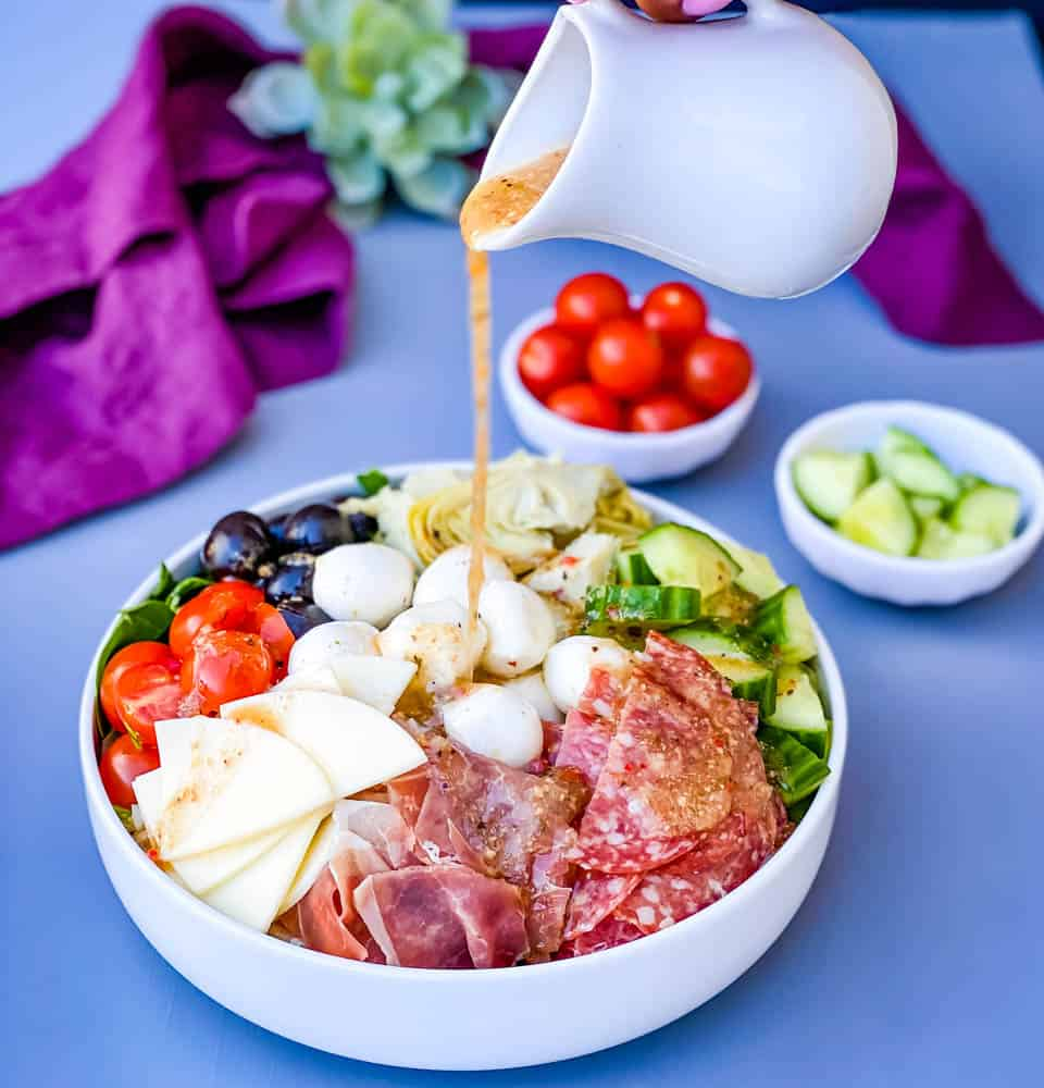 Italian dressing drizzled over antipasto salad in a white bowl