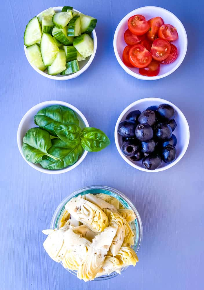 black olives, artichokes, cucumbers, and sliced cherry tomatoes in separate white bowls for antipasto salad recipe