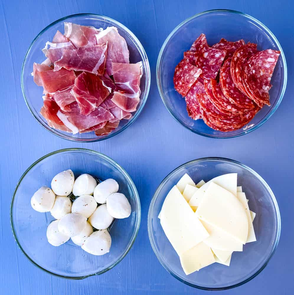 prosciutto, salami, mozzarella balls, and sliced provolone cheese in separate white bowls for antipasto salad recipe