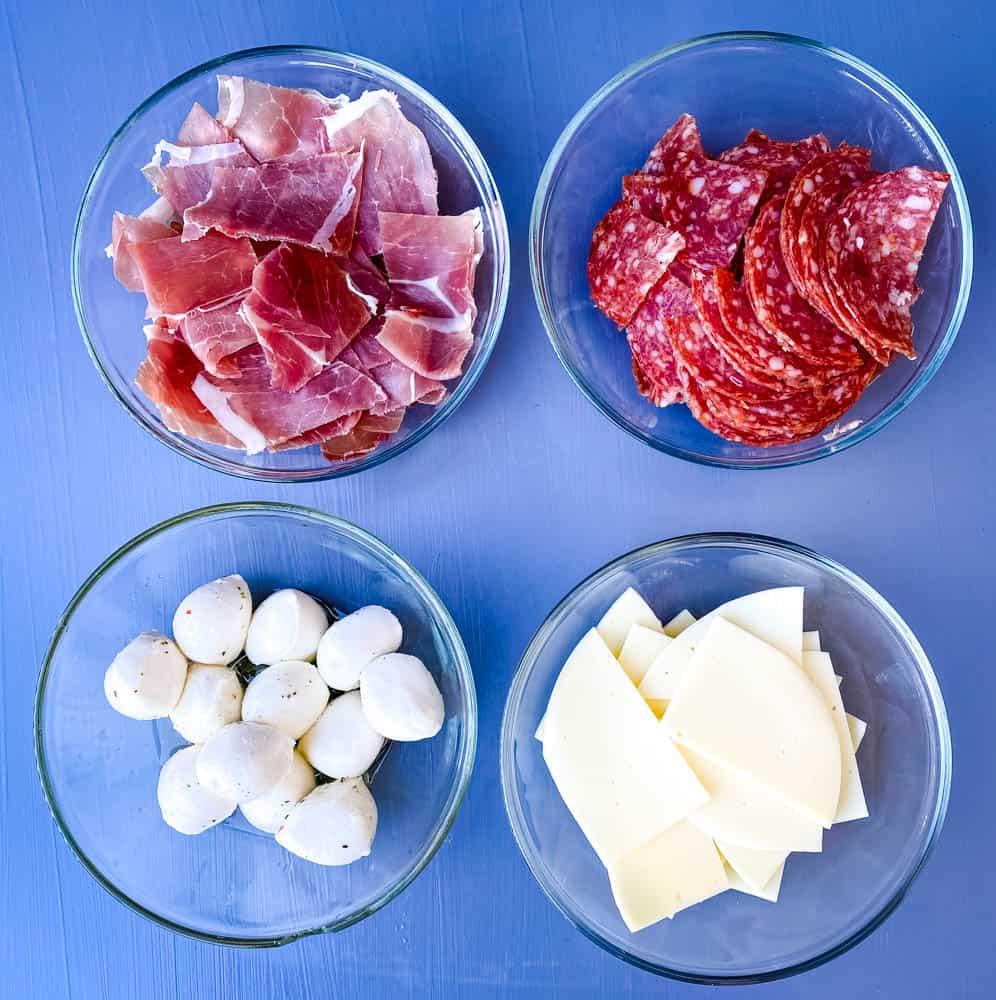 prosciutto, salami, mozzarella balls, and sliced provolone cheese in separate white bowls for antipasto salad recipe