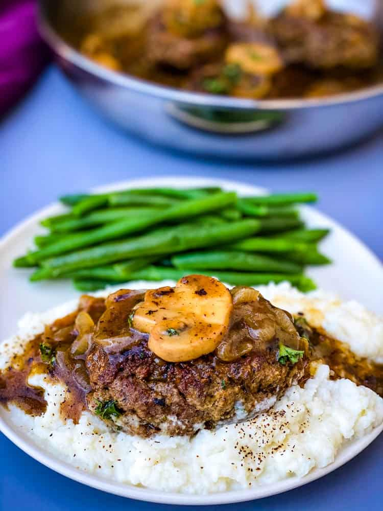 keto low carb salisbury steaks on mashed cauliflower with green beans on a white plate