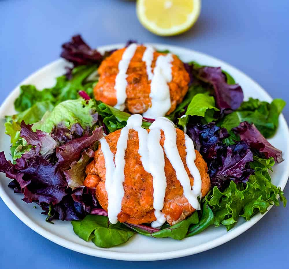keto low carb salmon patties on a plate with mixed greens and creamy garlic sauce