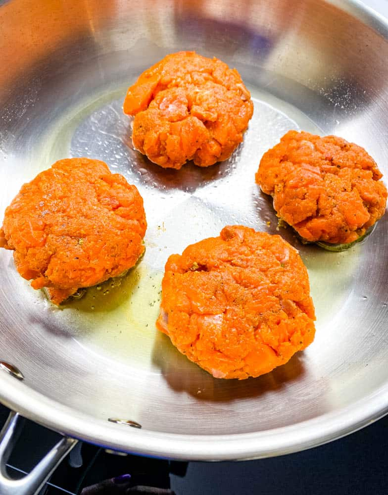 keto low carb salmon patties in a stainless steel frying pan